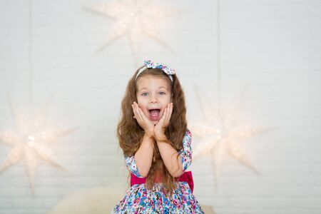 Cute little girl in a beautiful dress presses her hands to her face in surprise.