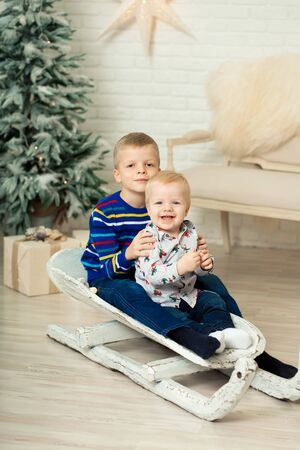 Christmas is already here. Two brothers sledding with christmas gift box. Small cute boy received holiday gifts. Kid hold gift box while sledding. Celebrate christmas. Winter activity.