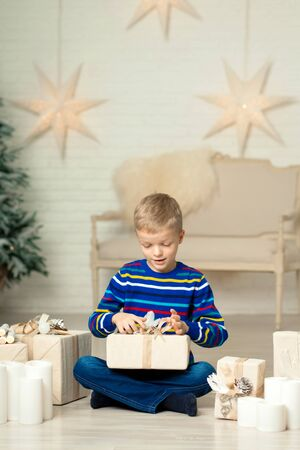Happy smiling boy holds christmas gift box against the background of New Years decor
