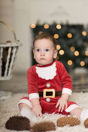 Portrait of a cute toddler playing on the floor with cones to decorate the Christmas tree. Near the Christmas tree and boxes with Christmas gifts. Merry Christmas and happy holidays