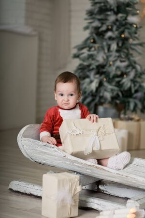 Christmas is already here. Boy sledding with christmas gift box. Small cute boy received holiday gifts. Kid hold gift box while sledding. Celebrate christmas. Winter activity Фото со стока