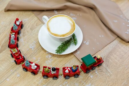 Delicious fresh festive morning cappuccino coffee in a ceramic white cup on the wooden table with decorative christmas train, red ornamentals, fireflies and spruce branches. Фото со стока
