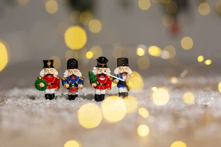 Decorative Christmas-themed figurines. Christmas toy soldiers from a nutcracker fairy tale. Christmas tree decoration. Festive decor, warm bokeh lights