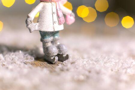 Decorative Christmas-themed figurines. Statuette of a man on skates. Christmas tree decoration. Festive decor, warm bokeh lights