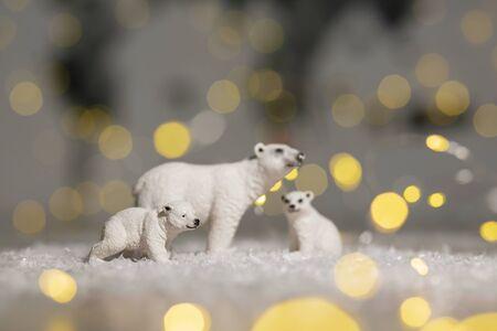 Decorative figurines of a Christmas theme. Statuettes of a family of polar bears. Christmas tree decoration. Festive decor, warm bokeh lights