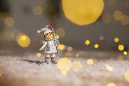 Decorative Christmas-themed figurines. Statuette boy in knitted hats and scarves. Christmas tree decoration. Festive decor, warm bokeh lights