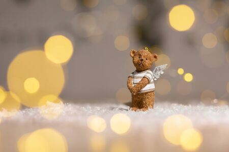Decorative figurines of a Christmas theme. Figurine of a cute bear with angel wings. Festive decor, warm bokeh lights. Фото со стока