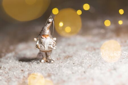 Decorative Christmas-themed figurines. Statuette of a gnome with a white beard and a gift. Christmas tree decoration. Festive decor, warm bokeh lights