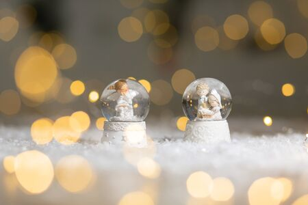 Decorative Christmas-themed figurines. Glass ball with snowflakes in which the Christmas angel sits, a symbol of the Nativity of Christ. Christmas tree decoration. Festive decor, warm bokeh lights