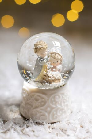 Decorative Christmas-themed figurines. A glass ball with snowflakes in which two men are looking at the cradle, a symbol of the Nativity of Christ. Christmas tree decoration. Festive decor, warm bokeh lights Фото со стока