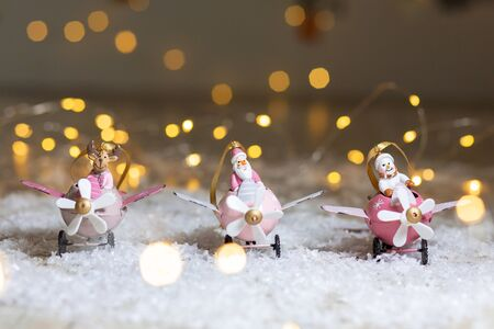 A set of decorative Christmas-themed statuettes. Santa claus deer and snowman in pink airplanes with propeller. Festive decor, warm bokeh lights