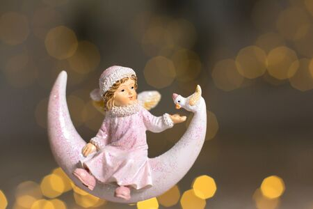 Decorative figurines of a Christmas theme. Statuette of an angel on a crescent moon. Christmas tree decoration. Festive decor, warm bokeh lights