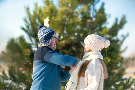 guy wraps a girl in a warm white scarf while walking through a snowy winter forest.