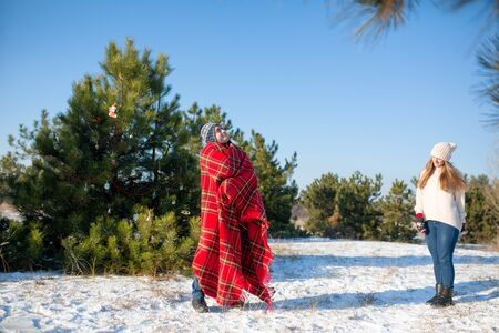 winter walk in the forest. A guy in a red plaid plaid poses like a superhero, considering that the plaid is his cloak. The superhero we deserve. Stock Photo