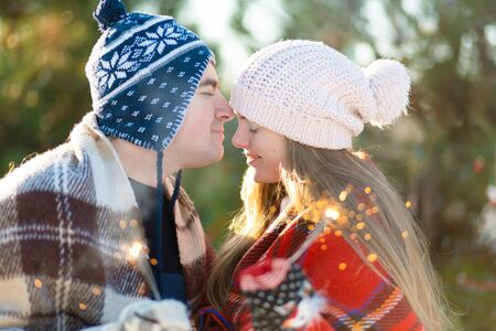 A loving couple in warm plaids kisses holding sparklers in their hands. Meet the winter holidays in a snowy forest.
