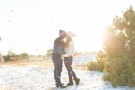 The guy with the girl kiss in the winter in the woods against the background of falling candy. Romantic winter atmosphere.