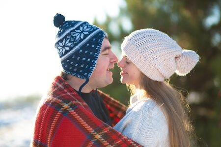 Winter walk through the woods. The guy with the girl kissed wrapped in a red checkered plaid. Stock Photo
