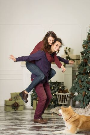 A young couple with a dog fooling around near a Christmas tree. Happy new year and merry christmas. Stock Photo - 133210244