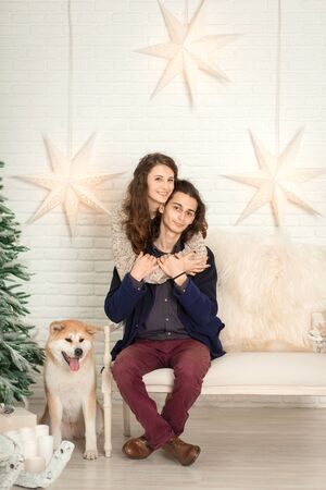 Christmas decorations. Young happy couple cuddling and kissing while sitting on a bench next to a dog. Reklamní fotografie