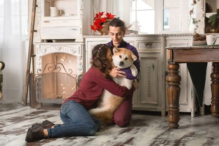Cheerful young couple is hugging and kissing a dog of Akita Inu breed. in Christmas decorations in retro style. Reklamní fotografie - 133209727
