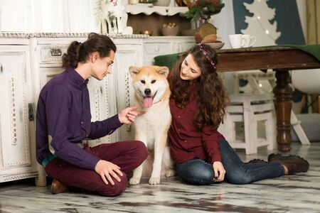 Cheerful young couple is hugging and kissing a dog of Akita Inu breed. in Christmas decorations in retro style.