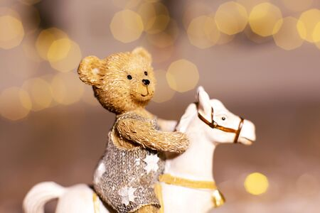 Decorative figurines of a Christmas theme. Figurine of a little teddy bear on a rocking horse. Christmas tree decoration. Festive decor, warm bokeh lights
