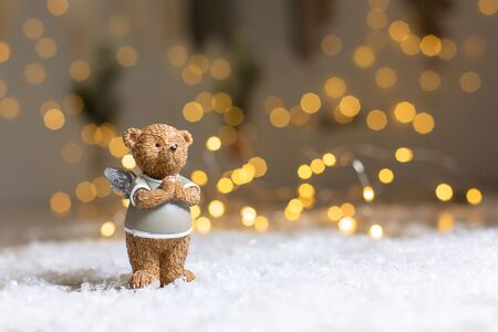 Decorative figurines of a Christmas theme. Figurine of a cute bear with angel wings. Festive decor, warm bokeh lights. Stock Photo
