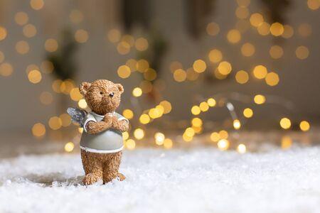 Decorative figurines of a Christmas theme. Figurine of a cute bear with angel wings. Festive decor, warm bokeh lights. 免版税图像