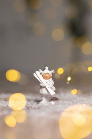 Decorative Christmas-themed figurines. Statuette A little man in a white suit with white skis. Christmas tree decoration. Festive decor, warm bokeh lights