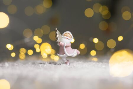 Decorative figurines of a Christmas theme. Santa statuette hugging a small Christmas tree. Christmas tree decoration. Festive decor, warm bokeh lights Archivio Fotografico
