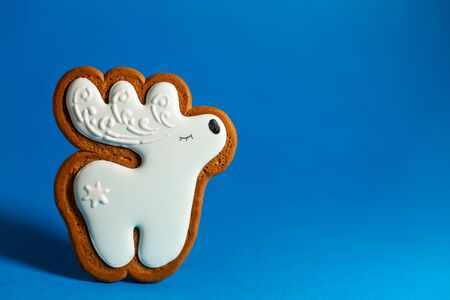 gingerbread cookie of cute deer on blue background. Traditional Christmas food. Christmas and New Year holiday concept