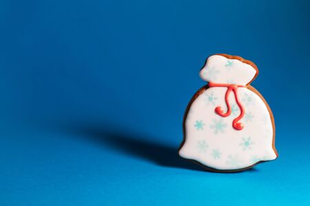 gingerbread cookie of Santas bag on blue background. Traditional Christmas food. Christmas and New Year holiday concept. Copyspace.