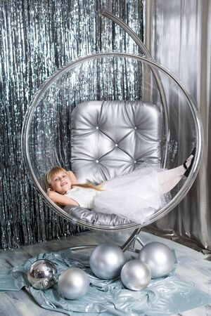 Little girl plays in a chair a glass bowl with silver balls. Snow queen cover Фото со стока