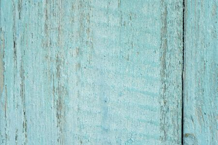 old wooden fence light blue paint peeling board texture. Background. Фото со стока