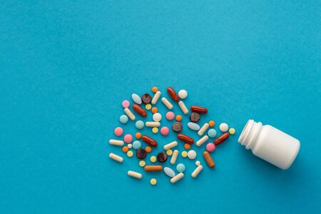 A handful of colored pills spilled out of the can on a blue background. Medical concept. Фото со стока