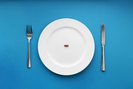 A small tablet in a plate. Medical concept. Eat pills instead of food