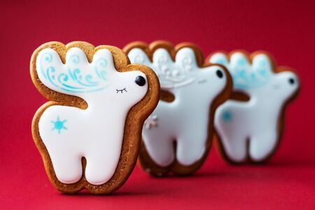 gingerbread cookie of little cute deer on red background. Traditional Christmas food. Christmas and New Year holiday concept Фото со стока