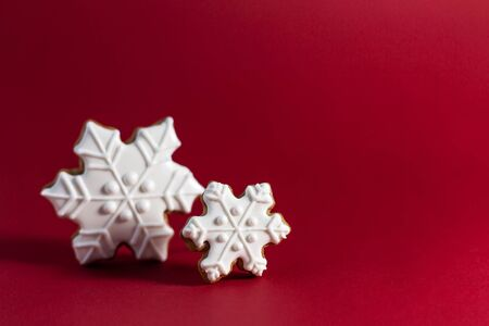 gingerbread cookie of snowflake on red background. Traditional Christmas food. Christmas and New Year holiday concept