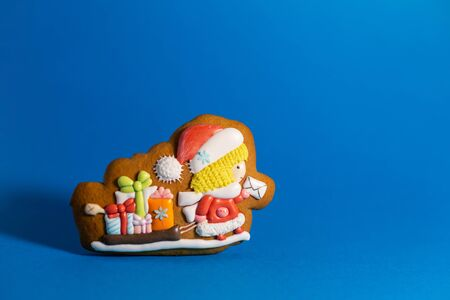 gingerbread cookie of little cute Santa postman on blue background. Traditional Christmas food. Christmas and New Year holiday concept. Copyspace. Фото со стока