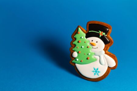gingerbread cookie of cute snowman with green christmas tree on blue background. Traditional Christmas food. Christmas and New Year holiday concept
