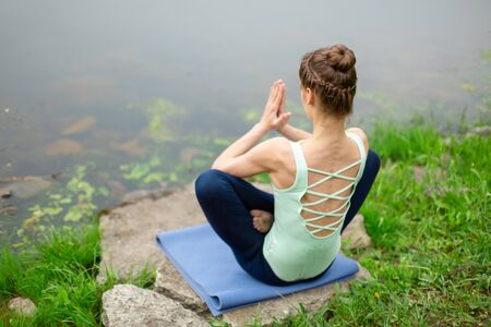 A young sports girl practices yoga on a green lawn by the river, assans posture. Unity with nature Imagens - 133385152