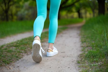 A young sports girl running in a quit green summer forest. Sport and wellness. Фото со стока