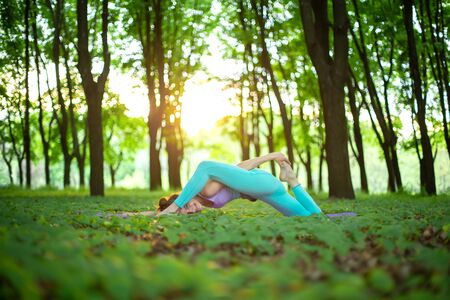 A young sports girl practices yoga in a quit green summer forest, yoga assans posture. Meditation and unity with nature. Reklamní fotografie