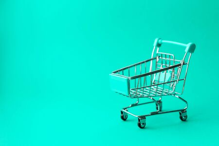 empty metal shopping trolley on green background. Discount and shopping concept.