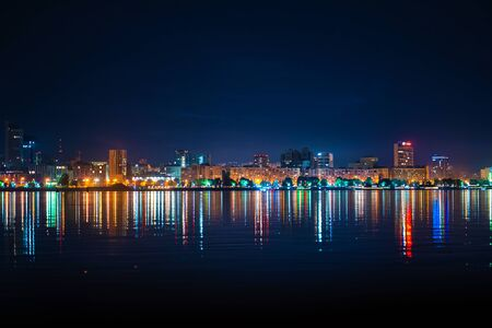 night landscape of the city promenade with many colored lights reflected in the water.