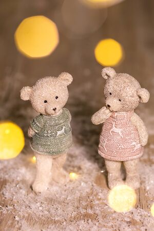 Decorative figurines of a Christmas theme. Figurines of cute teddy bears of a boy and a girl in sweaters with deers. Festive decor, warm bokeh lights Stock fotó