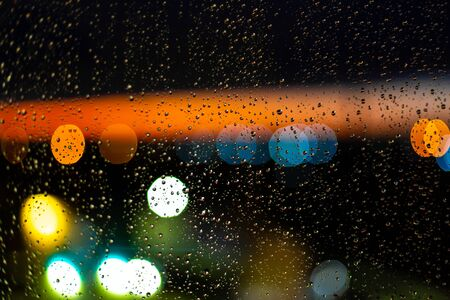 Water drop at windows and bokeh of city in sunset. Reklamní fotografie