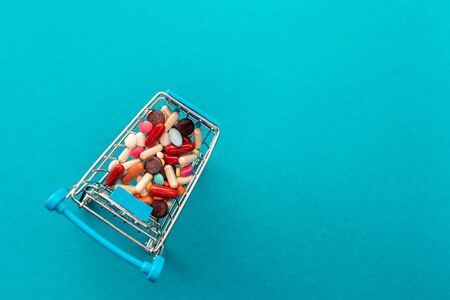 Cart from the supermarket filled with colored pills. Medical concept. Shopping at the pharmacy