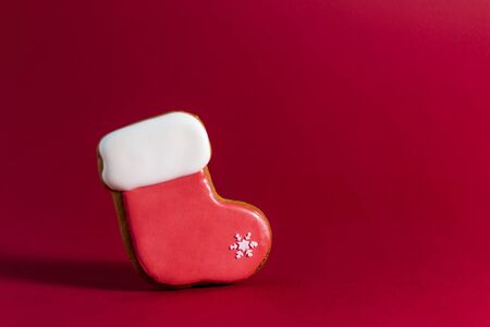 gingerbread cookie of Santas sock on red background. Traditional Christmas food. Christmas and New Year holiday concept. Copyspace. Reklamní fotografie