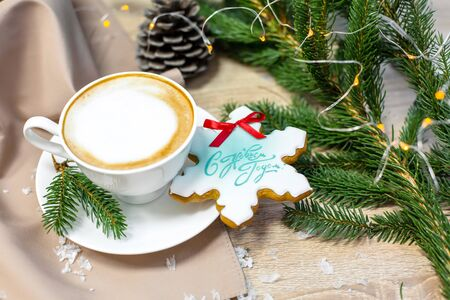 Christmas and happy new year card with cup of coffee, pine, fir branch and gingerbread on wooden table background, copy space, top view. Reklamní fotografie